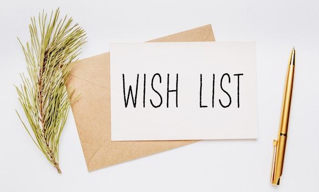 Wenslijst notitie met envelop, vuren tak en gouden pen op witte achtergrond. vrolijk kerstfeest en nieuwjaarsconcept