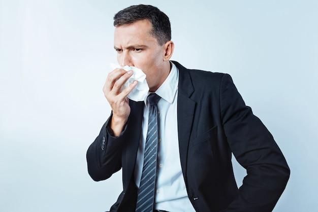 Werd ziek. taille-up shot van een gefrustreerde zakenman die een vacature onderzoekt terwijl hij een servet gebruikt en niest tegen de lichte achtergrond.