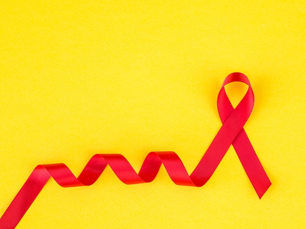 Wereld aidsdag concept. rood lint op gele achtergrond.