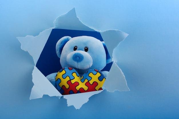 Wereld autisme bewustzijn, concept met teddybeer met puzzel of puzzel patroon op hart in papier gesneden gat