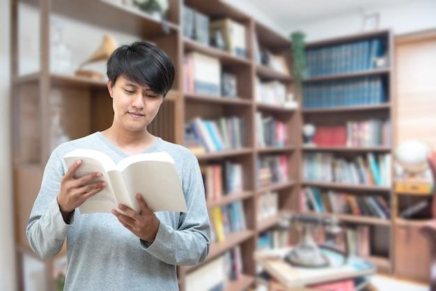 Wereld boek dag concept. jonge aziatische man universiteitsstudent leesboek zitten door boekenplank in college bibliotheek voor onderwijs onderzoek en zelfverbetering. beurs en educatieve mogelijkheid.