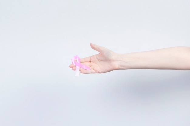 Wereld borstkanker dag concept. vrouw houdt roze lint in haar hand. maand van de voorlichting van borstkanker in oktober