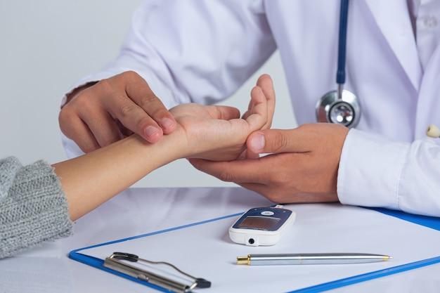 Wereld diabetes dag; arts controleert de pols van de patiënt