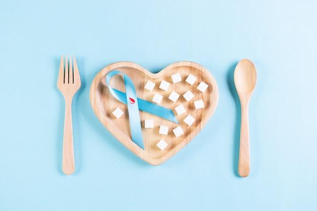 Wereld diabetes dag. blauw lint met bloeddruppel erin en suiker op plaat op pastelblauw