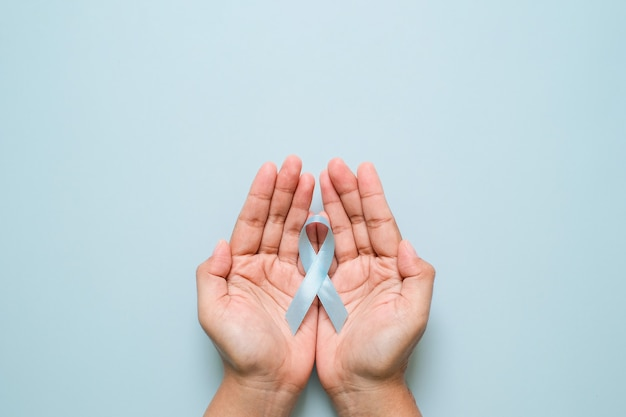 Wereld diabetes dag en blauw lint bewustzijn met rode bloeddruppel in handen van de vrouw geïsoleerd op een blauwe achtergrond. werelddiabetesdag, 14 november. ruimte kopiëren. bovenaanzicht