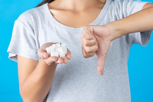 Wereld diabetes dag; hand met suikerklontjes en duim omlaag in een andere hand