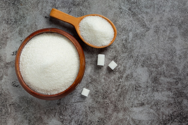 Wereld diabetes dag; suiker in houten kom op donkere achtergrond