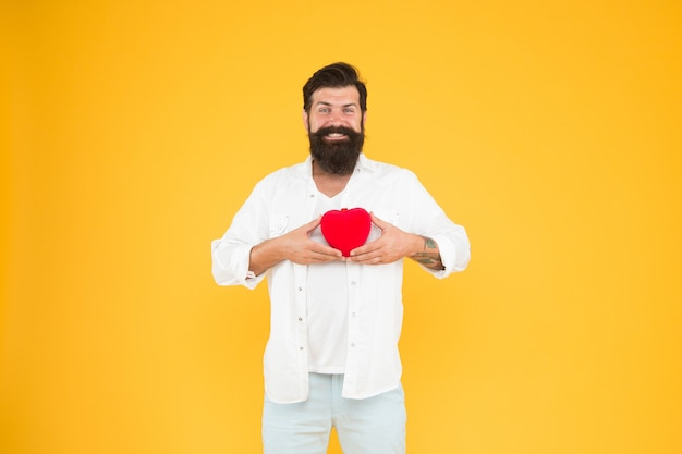 Wereld hart dag. brutale hipster gele achtergrond. fijne valentijnsdag. hartproblemen en ziekte. met gezonde gewoonten in levensstijl. hartaanval voorkomen. verliefd worden. bebaarde man rood hart.
