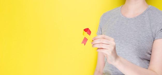 Wereld hepatitis dag-concept. meisje in grijs t-shirt houdt in haar hand bewustzijn symbool rood-geel lint. gele achtergrond. ruimte kopiëren