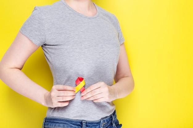 Wereld hepatitis dag concept. meisje in grijs t-shirt met rood-geel lintgebied liveras symbool van bewustzijn.
