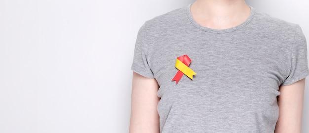 Wereld hepatitis dag concept. meisje in grijs t-shirt met vastgemaakt bewustzijnssymbool rood-geel lint. grijze achtergrond. ruimte kopiëren