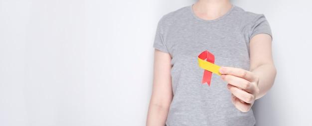 Wereld hepatitis dag concept meisje in grijze tshirt houdt in de hand bewustzijn symbool roodgeel lint