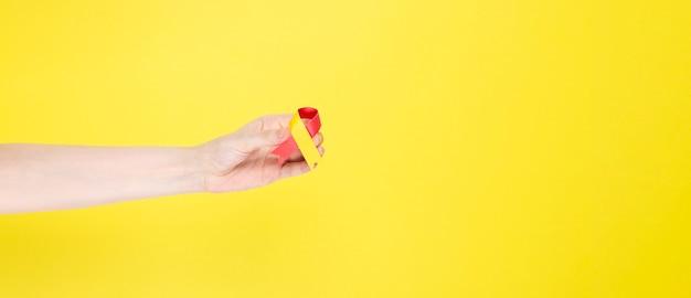 Wereld hepatitis dag concept. vrouw houdt in haar hand bewustzijn symbool rood-geel lint. gele achtergrond. kopieer ruimte