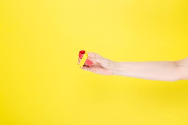Wereld hepatitis dag-concept. vrouw houdt in haar hand bewustzijn symbool rood-geel lint. gele achtergrond. ruimte kopiëren