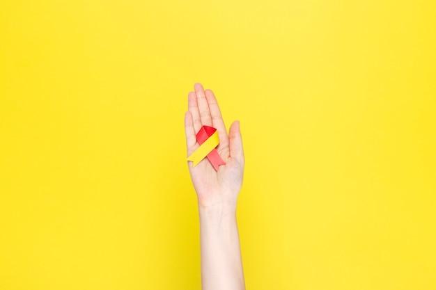 Wereld hepatitis dag concept. vrouw houdt in haar hand bewustzijn symbool rood-geel lint Premium Foto