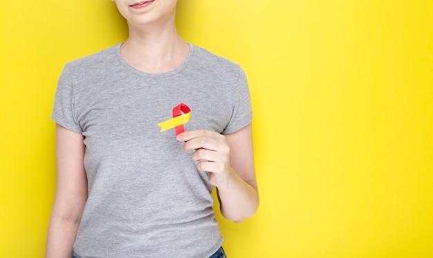Wereld hepatitis day concept. het meisje houdt in haar hand het rood-gele lint van het voorlichtingssymbool Premium Foto