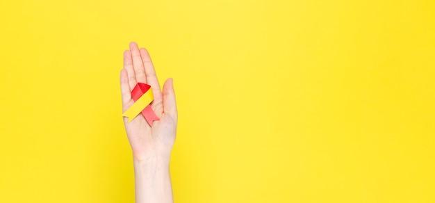 Wereld hepatitis day concept. vrouw houdt voorlichtingssymbool rood-geel lint