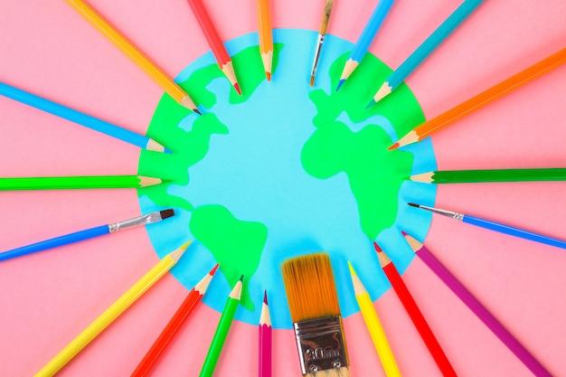 Wereld kunst. planeet aarde en potloden, borstels op een pastel roze achtergrond.