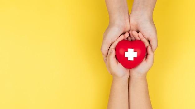 Wereld rode kruis dag, volwassen en kind handen met rood hart