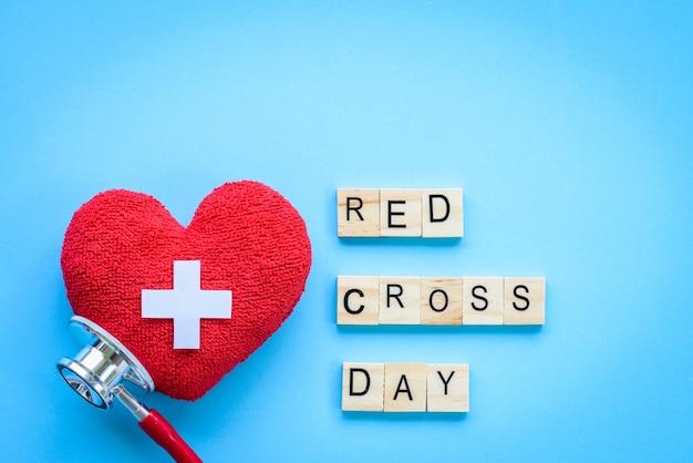 Wereld rode kruisdag, rood hart met stethoscoop op blauwe achtergrond.
