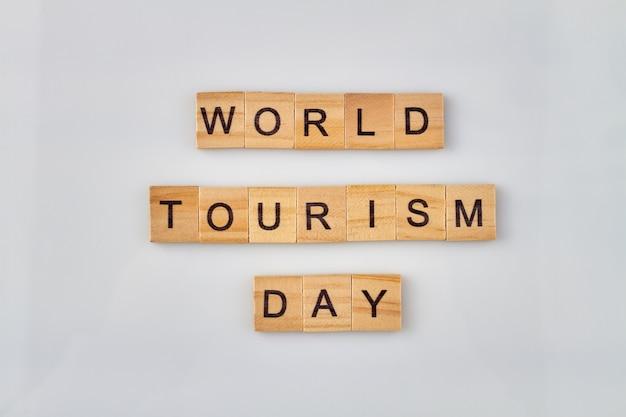 Wereld toerisme dag concept. alfabet houten blokken met letters op een witte achtergrond.