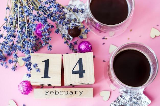 Wereld valentijnsdag. houten kalender met datum 14 februari op roze achtergrond met koffie en snoep