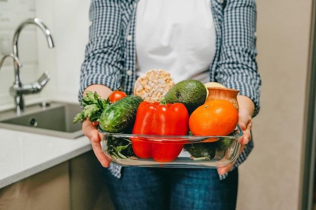 Wereld vegan dag verschillende rauwe groenten, kruiden en granen in vrouwelijke handen vers rauw voedsel seizoensgebonden