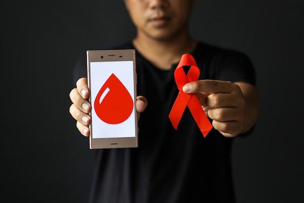 Wereldaidsdag of werelddiabetesdag met mannelijke handen met rood aidslint en bloedsymbool