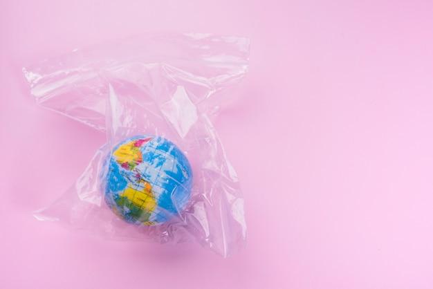 Wereldbol in polyethyleen zak over roze achtergrond