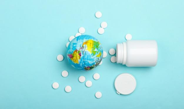 Wereldbol met een fles pillen op een blauw oppervlak