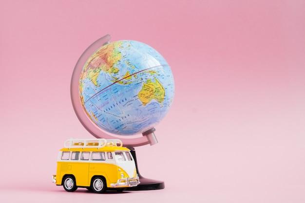 Wereldbol met gele busje op roze