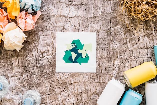 Wereldbol met recycle pictogram omringd door vuilnis