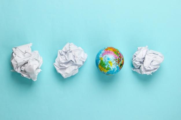 Wereldbol met verfrommeld papier ballen op een blauw. concept kunst.