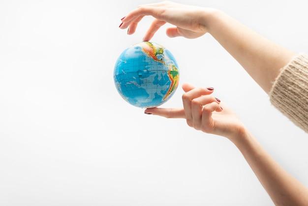 Wereldbol op het puntje van de vingers. vrouwelijke hand houdt wereldbol. wereld in mensenhanden.