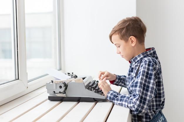 Werelddag van het concept van de schrijver - jongen met een oude typemachine.