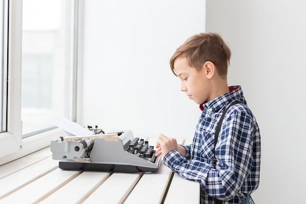 Werelddag van het schrijverconcept - jongen met een oude typemachine over raamoppervlak