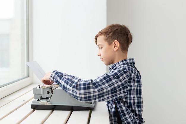 Werelddag van het schrijverconcept - jongen met een oude typemachine over venstermuur.