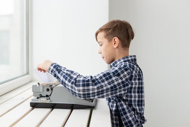 Werelddag van het schrijverconcept - jongen verandert het papier in de typemachine