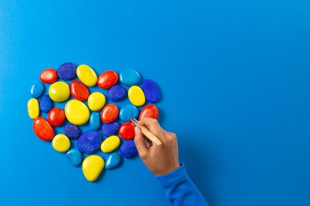 Werelddag voor autisme-bewustzijn. kid hand schilderen met borstel hart gemaakt van stenen in blauw rood gele kleuren