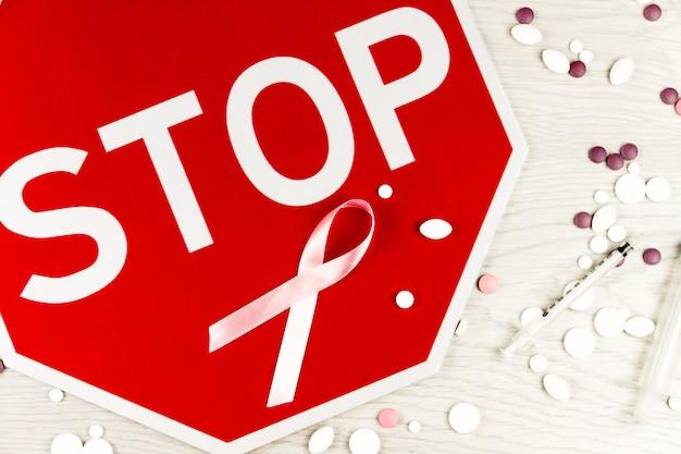 Werelddag voor kankerconcept. roze lint als symbool van borstkanker, tekenstop, pillen en spuiten die op lichte houten lijst worden geïsoleerd