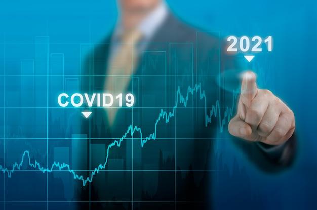 Wereldeconomieconcept van economisch herstel na de val als gevolg van de covid 19-coronaviruspandemie. zakenman aanwijsapparaat grafiek corporate toekomstig groeiplan op donkerblauw. herstart economie na crisis