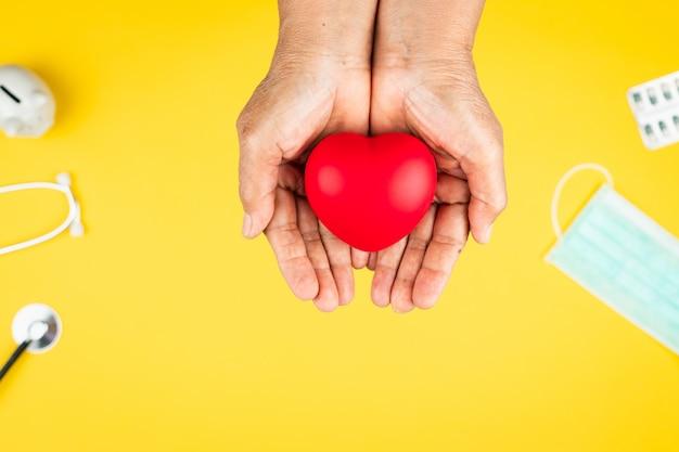 Wereldgezondheidsdag concept gezondheidszorg ziektekostenverzekering met rood hart op senior handen van de vrouw ondersteuning
