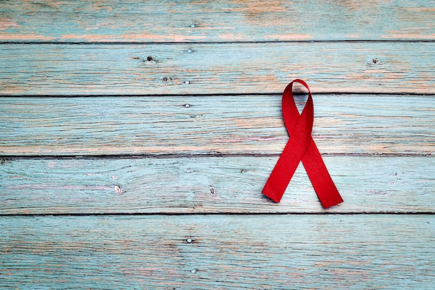 Wereldgezondheidsdag, gezondheidszorg en medisch concept, rood lint op de blauwe houten achtergrond