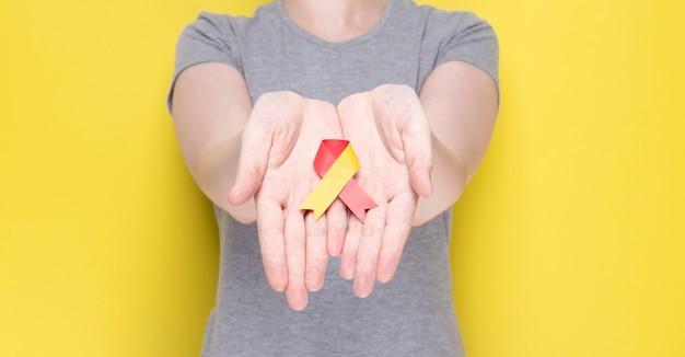 Wereldhepatitisdagconcept, vrouw met een rood en geel lint in haar handen op gele achtergrond
