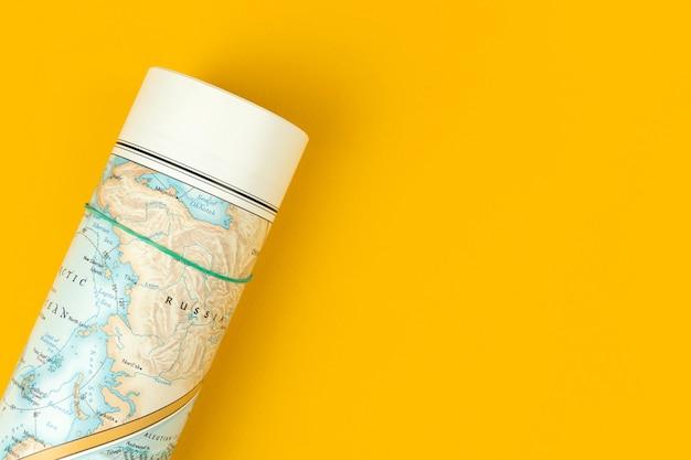 Wereldkaart op de tafel plat liggende compositie en gele bureaubladachtergrond bovenaanzicht en kopieer ruimtefoto