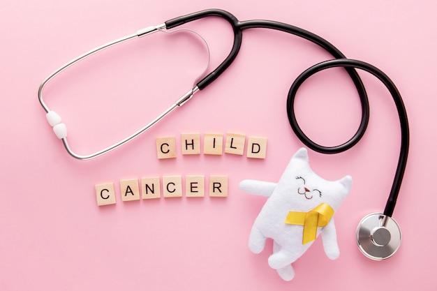 Wereldkanker dag voor kinderen, witte kat met geel lint, stethoscoop en kanker dag bericht