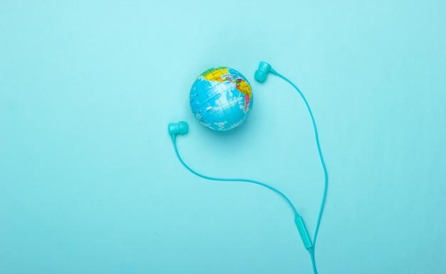 Wereldlied. wereldwijde muziekgrafiek. de muziek van de aarde. stereo oortelefoons en een wereldbol op een blauwe muur bovenaanzicht