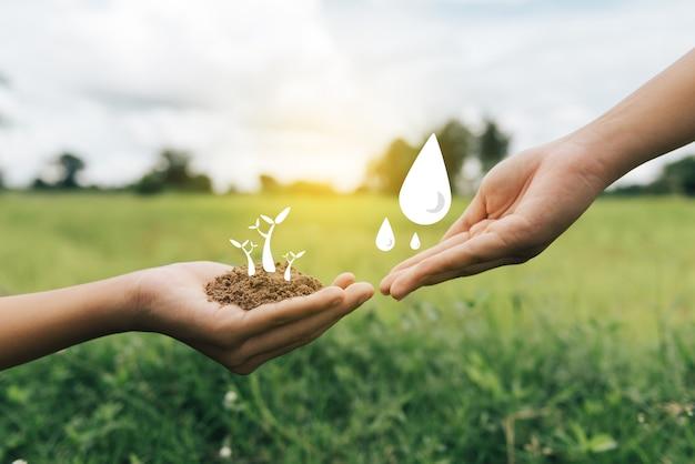 Wereldmilieudag groene achtergrond hand met boom op natuurveldgras