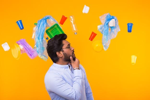 Wereldmilieudag, plastic recyclingprobleem en milieurampconcept - ernstige indische mens die op afval kijkt