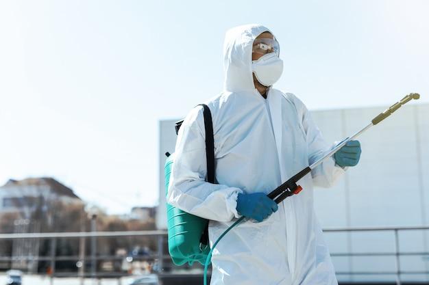 Wereldpandemie. desinfector in een beschermend pak en masker, met desinfecterende chemicaliën buitenshuis